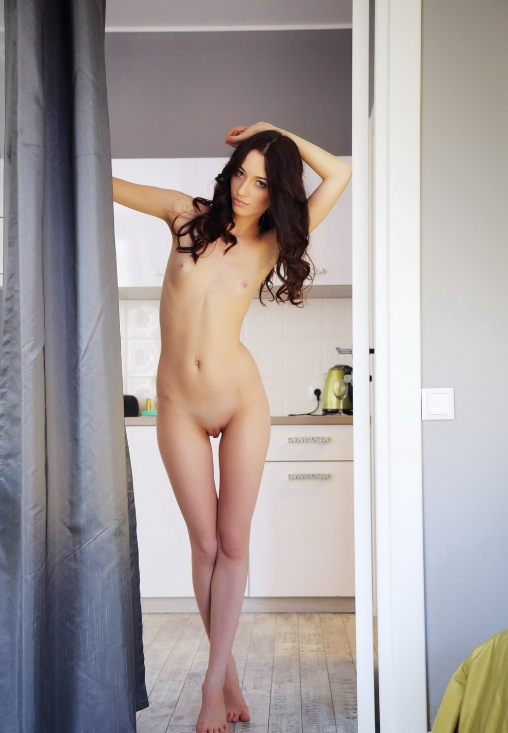 Petite brunette standing in the kitchen