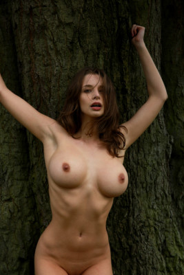 Stunning brunette by a tree