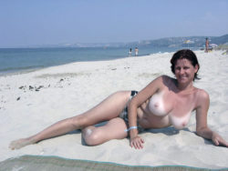 Milf with nice tits topless at the beach