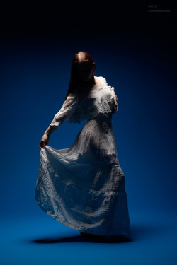 Silhouetted woman in white dress.