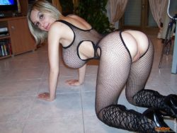 Busty babe with a fat pussy in a fishnet body suit.