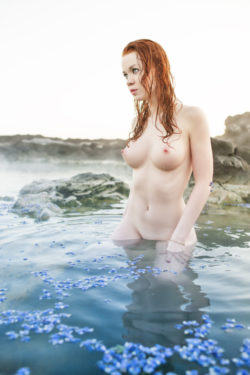 Busty red head in a blue lagoon