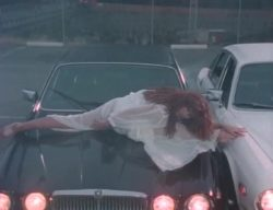 Tawny Kitaen on the hood of a car with some classic 80's music video plot